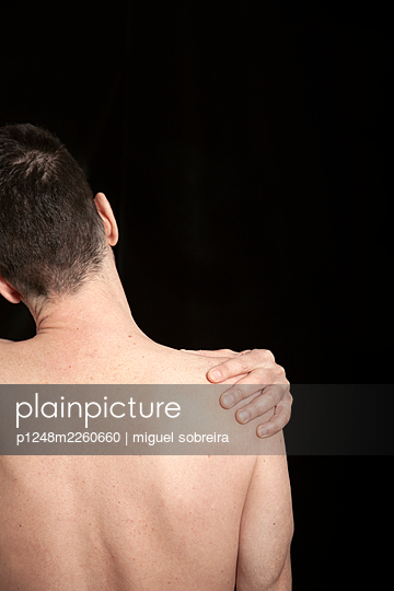 Shirtless man holding his shoulder - p1248m2260660 by miguel sobreira