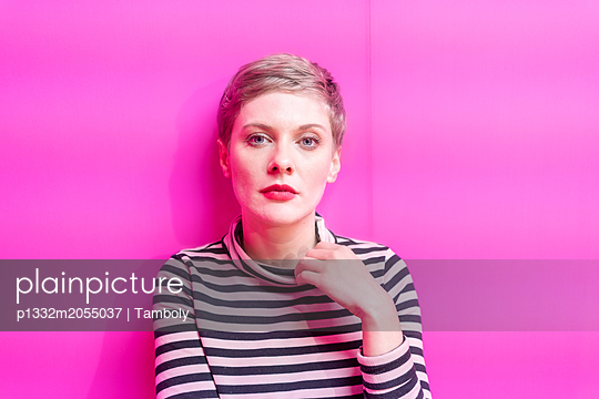 Woman in front of a pink wall - p1332m2055037 by Tamboly