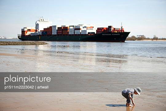 Kind am Elbufer, Containerschiff im Hintergrund - p1511m2223042 von artwall