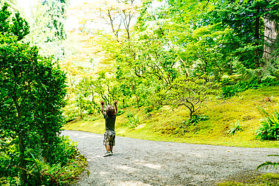 A young boy lifts his hands in the air as he walks down a path - p1166m2084244 by Cavan Images