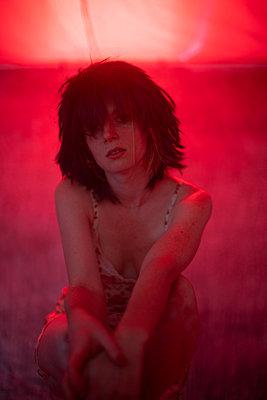 Junge Frau in rotem Licht - p1321m2141709 von Gordon Spooner