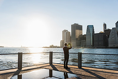 USA, Brooklyn, back view of man taking picture of Manhattan skyline with tablet - p300m1205776 by Uwe Umstätter