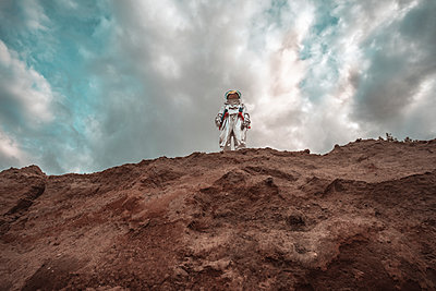 Spaceman standing on slope of nameless planet - p300m2023778 by Vasily Pindyurin