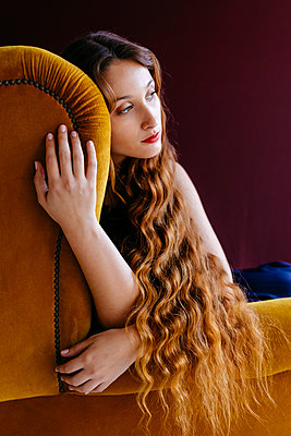 Thoughtful young woman with long brown wavy hair sitting on golden chair against colored background - p300m2198944 by Tania Cervián