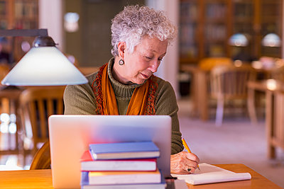 Older mixed race woman using laptop in library - p555m1306133 by Marc Romanelli