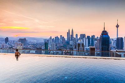 Man in a infinity pool overlooking Kuala Lumpur skyline, Malaysia - p651m2062170 by Matteo Colombo photography