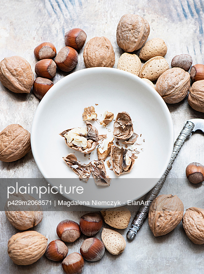 Walnuts and almonds in shell, hazelnuts, cracked walnut in bowl - p429m2068571 by Magdalena Niemczyk - ElanArt