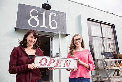 Two young Caucasian women owners of a new antique store. - p1100m1575574 by Mint Images