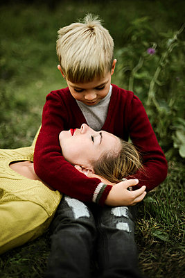 Son embracing mother on field in the countryside - p1166m2096085 by Cavan Images