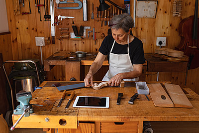 Female luthier at work in a workshop - p1315m2131458 by Wavebreak