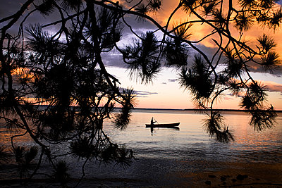 A man canoes during sunset on beautiful Sebago Lake in Maine, USA. - p1424m1501902 by Todd Korol