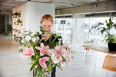 Smiling woman with bunch of flowers at home - p300m2265245 by Jo Kirchherr