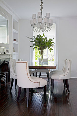 White dining chairs at table with leaf arrangement under chandelier in London home  UK - p3493421 by Robert Sanderson