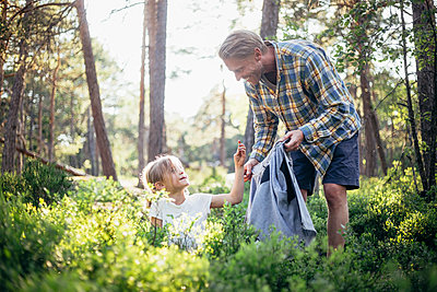 Smiling father looking at daughter collecting garbage in forest - p426m2213263 by Maskot