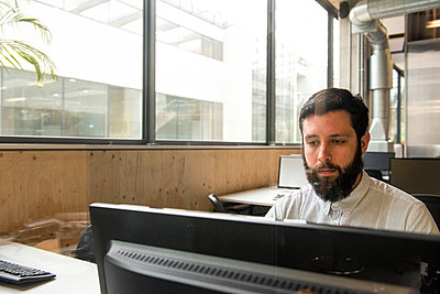 Man in office using desktop computer - p429m1513873 by G. Mazzarini