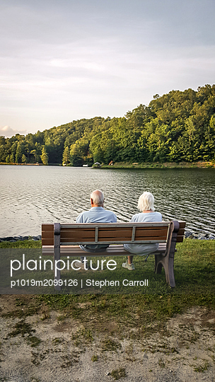 Senior couple sitting on bench, rear view - p1019m2099126 by Stephen Carroll