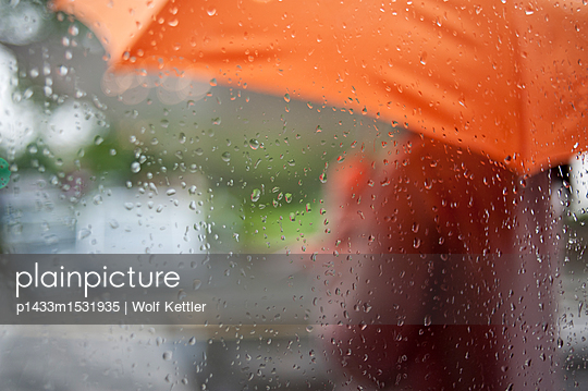 A blurred female figure with an orange umbrella seen through window with raindrops. - p1433m1531935 by Wolf Kettler
