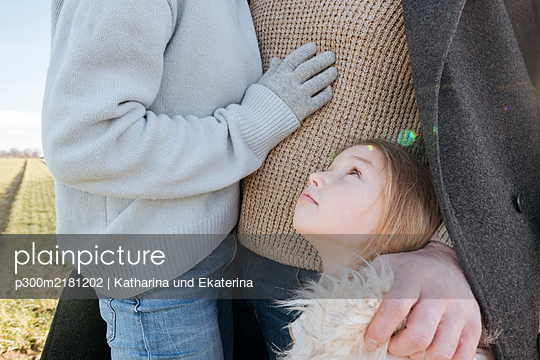 Little girl outdoors with her parents in winter - p300m2181202 by Katharina und Ekaterina