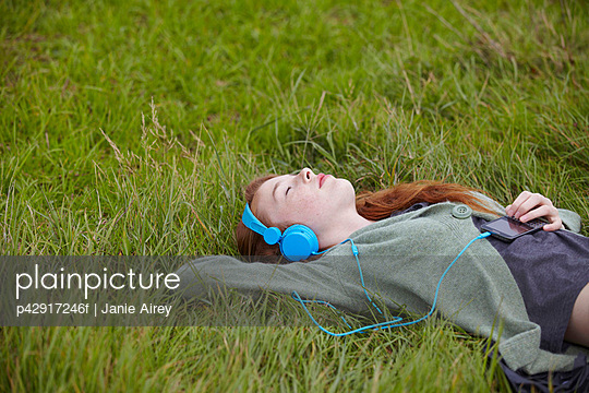 Teenage girl listening to headphones - p42917246f by Janie Airey