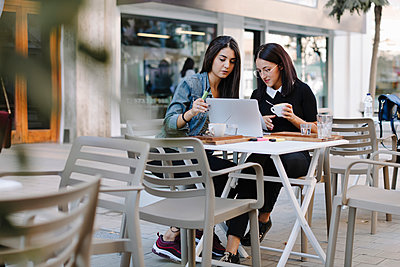 Two friends sitting together at a pavement cafe using laptop - p300m2103488 von Oriol Castelló Arroyo