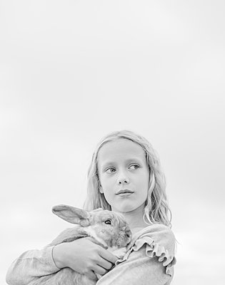 Blonde girl holding rabbit in arms - p552m2124864 by Leander Hopf