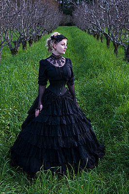 Woman in orchard wearing Victorian clothing  - p920m1573730 by Jude Mooney
