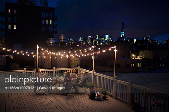 Young people sitting under fairy lights at roof terrace