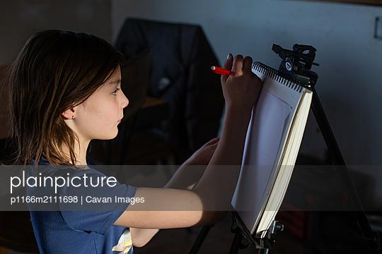 Tween girl drawing at an easel - p1166m2111698 by Cavan Images