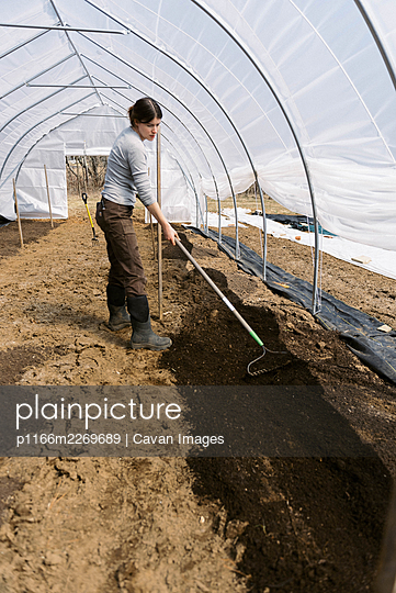 A young female farmer working in green house in the morning in spring - p1166m2269689 by Cavan Images