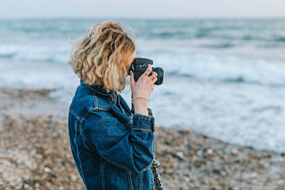 Young woman taking photographs from beach, Menemsha, Martha's Vineyard, Massachusetts, USA - p924m2058129 by Lena Mirisola