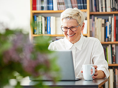 Portrait of laughing senior woman using digital tablet at home - p300m1153936 by Dieter Schewig