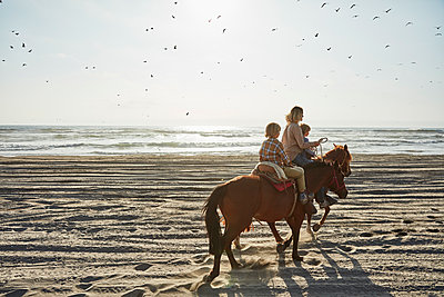 Chile, Vina del Mar, mother with two sons riding horses on the beach - p300m2070613 by Stefan Schütz