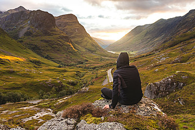 UK, Scotland, Man looking at view with the Three Sisters of Glencoe mountains on the left and the A82 road in the middle of the valley - p300m2081394 by William Perugini