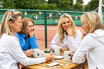 Group of women talking in a cafe at tennis club after a match - p300m2132620 von William Perugini