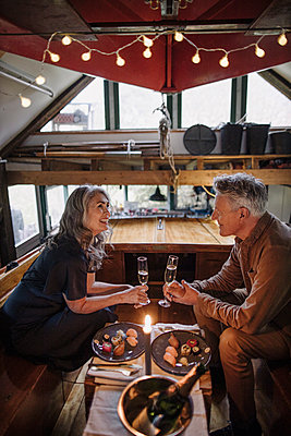 Senior couple having a candlelight dinner on a boat in boathouse - p300m2155247 von Gustafsson