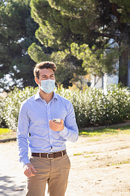 Businessman wearing protective face mask using mobile phone while standing on footpath - p300m2242618 by Ignacio Ferrándiz Roig