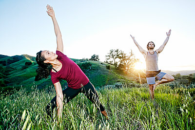 Couple practicing yoga on hill - p555m1303369 by Peathegee Inc