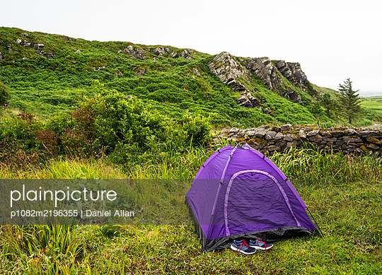 Purple tent and trainers in rocky landscape - p1082m2196355 by Daniel Allan