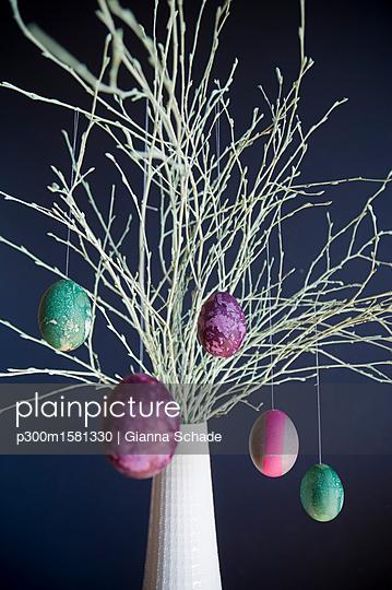 Sprayed twigs with dyed Easter eggs - p300m1581330 von Gianna Schade