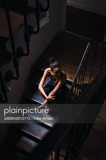 Beautiful young woman sitting in staircase in sunlight - p300m2012715 von Kike Arnaiz