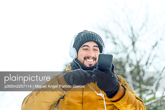 Man listening music through headphones while using mobile phone against sky - p300m2257114 by Miguel Angel Partido Garcia