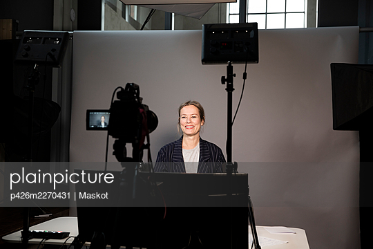 Smiling female entrepreneur video recording on television camera in office - p426m2270431 by Maskot