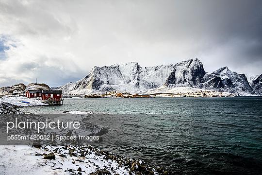 Snowy mountains overlooking rocky coastline, Reine, Lofoten Islands, Norway - p555m1420082 by Spaces Images