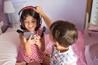 Portrait of smiling girl listening music with headphones while her little brother disturbing her - p300m2029285 von Jaen Stock