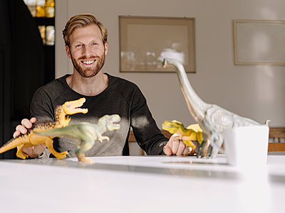 Portrait of smiling man with toy dinosaurs on table - p300m2205511 by Kniel Synnatzschke
