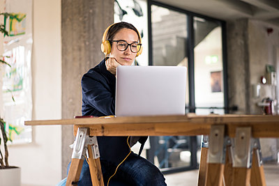 Businesswoman wearing headphones using laptop while sitting by table at office - p300m2226303 by Robijn Page