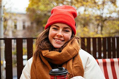 Young woman wearing knit hat and scarf smiling while sitting at sidewalk cafe - p300m2267123 by alev