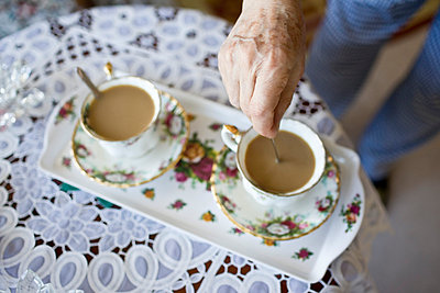 Elderly woman serves coffee in a pair of antique coffee mugs - p5350295 by Michelle Gibson