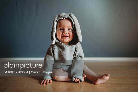 Adorable smiling baby wearing a bunny jumper for Easter - p1166m2269604 by Cavan Images