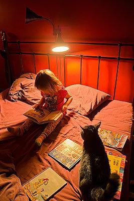 Kleines Mädchen liest ein Buch mit ihrer Katze - p1418m1590300 von Jan Håkan Dahlström
